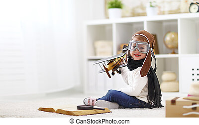 concept of dreams and travels.  pilot aviator child with a toy airplane