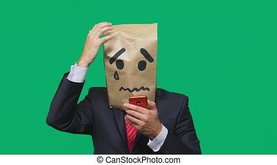 concept of emotion, gestures. a man with a package on his head, with a painted smiley crying, sad, talking on the phone