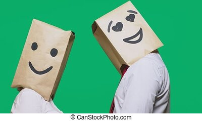 concept of emotions, gestures. a couple of people with paper bags on their heads, with a painted emoticon, smile, joy, eyes in love.