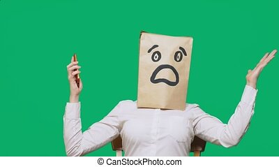 concept of emotions, gestures. a man with paper bags on his head, with a painted emoticon, fear. talking on a cell phone.