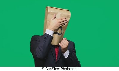 concept of emotions, gestures. a man with paper bags on his head, with a painted emoticon, fear