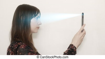 Concept of facial recognition. - Woman holding up her mobile...