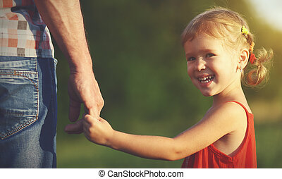 concept of family. child girl holding hand of dad