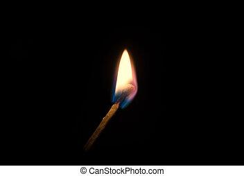 Burning match on a black background