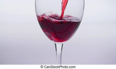 Concept of food and drinks. Red or pink wine poured into a glass on a white background in slow motion