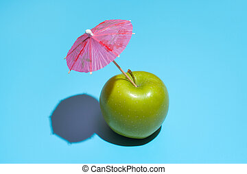 Concept of fresh green apple with a umbrella isolated on blue background.