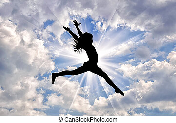 Silhouette of happy girl jumping