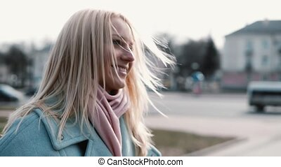 Concept of happy memories. Slow motion. Portrait of happy Caucasian woman side view. Flying blonde hair in counterlight.