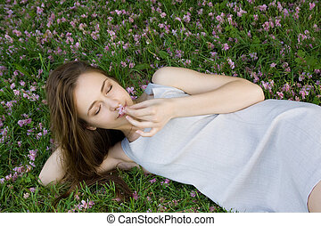 concept of harmony. Beautiful girl lying on green grass with flowers and holding a flower