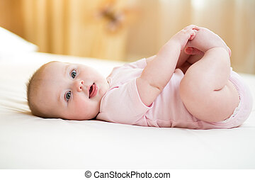 Concept of healthy child. Cute baby lying on her back on bed in room, holding legs with her hands.