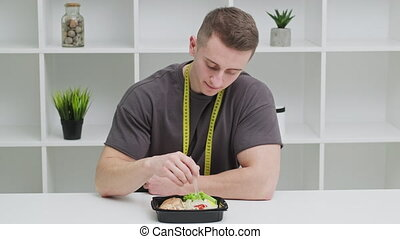 Concept of healthy eating, a man of athletic build eats ...