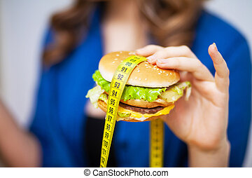 Concept of healthy eating, burger with yellow tape measure