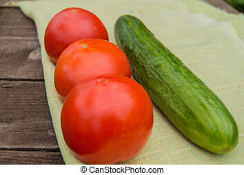 Concept of healthy eating with organic cucumber tomatoes, wooden background