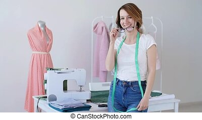 Concept of hobby and small business. Beautiful young female tailor smiling at camera in studio
