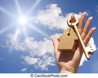 Concept of home ownership. Golden key in hand.