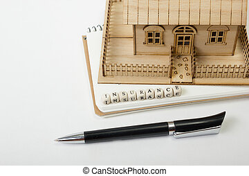 Concept of housing purchase and insurance. Office desk table with supplies top view. Pen, notepad, model house, wooden block word