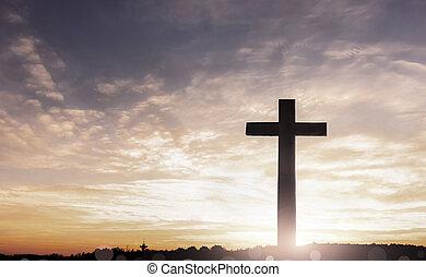 Concept of Jesus Christ:  cross on sunset sky background