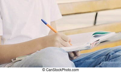 Young teenage boy in park sitting on the bench and writing their homework.