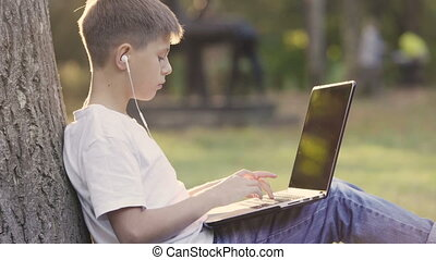 Young teenage boy in park sitting under tree in garden and using a laptop.