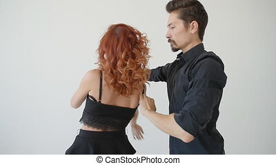 Concept of love and relationships. Beautiful young couple dancing in a white room