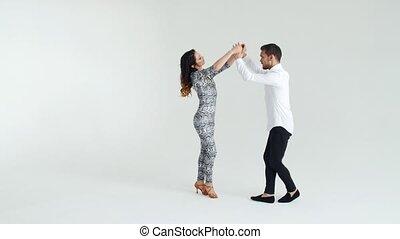 Concept of love, relationships and social dancing. Social dance, salsa, zouk, tango, kizomba concept - beautiful couple dancing bachata on white background
