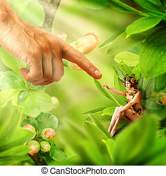 Human hand touching his finger to finger of garden fairy sitting on a green plant