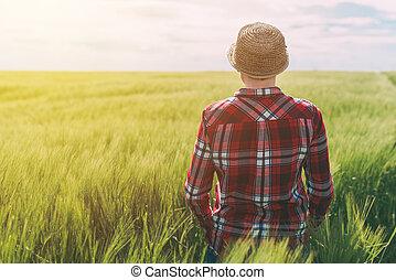 Concept of responsible farming, female farmer in cereal crops field