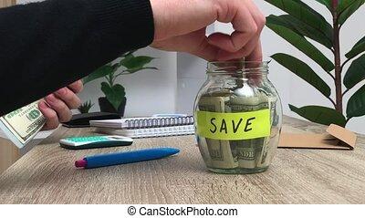 Concept of savings, a man puts 100 dollar bills in a glass jar