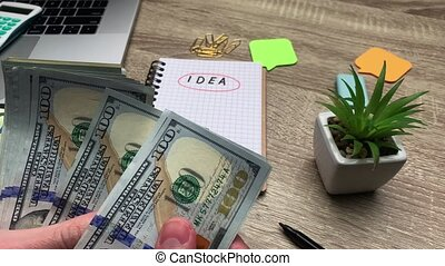 Concept of savings, man counts 100 dollars banknote to start his own business