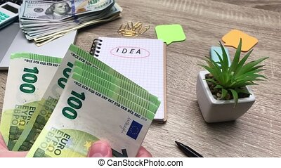 Concept of savings, man counts 100 euro banknote to start his own business.