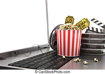 Concept of see online film. Film reels, clapperboard and pop corn on laptop keyboard.