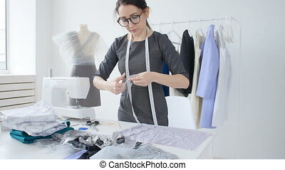 concept of small business and small production. Young dressmaker woman sews clothes in the workshop