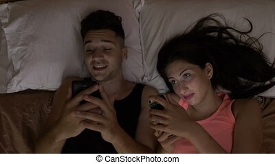 Concept of smartphone addiction married couple sitting in...