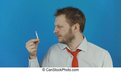 Concept of Smoking cessation or quitting smoking as a man looks at a cigarette