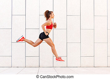Concept of sporting success. strong girl runs and jumps high against the background of the city wall