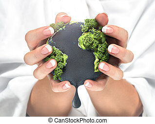 Concept of squeezing the resources of the planet. Ecology. Our planet in our hand. Woman hand holding planet Earth with oil in ocean.