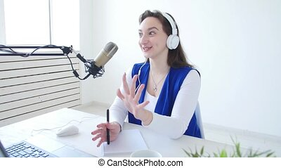 Concept of streaming and broadcasting. Young cheerful girl in the studio speaks into a microphone