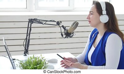 Concept of streaming and broadcasting. Young woman wearing headphones and talking at online radio station indoors