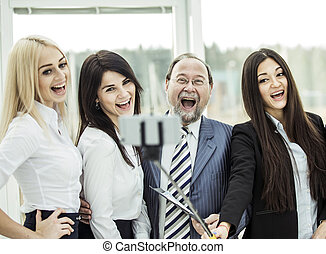 concept of success - boss and triumphant business team. on the background of the office