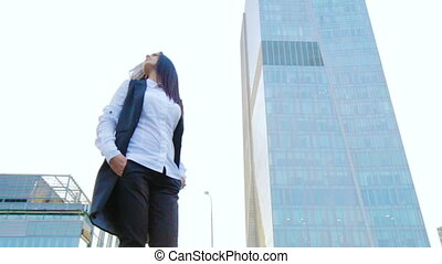 Concept of success - confident business woman looking around and standing against tall skyscraper