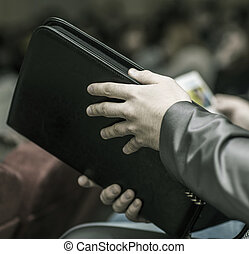 concept of success in business: a successful businessman with a folder for documents sitting in the conference room.