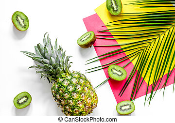 Concept of summer tropical fruits. Kiwi, pineapple and palm branch on white table background top view