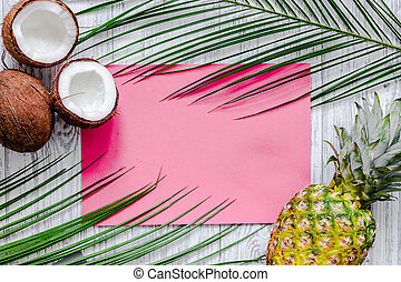 Concept of summer tropical fruits. Pineapple, cocount and palm branch on wooden table background top view mockup
