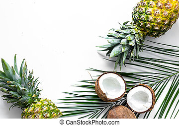 Concept of summer tropical fruits. Pineapple, cocount and palm branch on white background top view copyspace