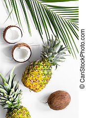 Concept of summer tropical fruits. Pineapple, coconut and palm branch on white background top view