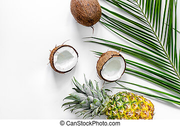 Concept of summer tropical fruits. Pineapple, coconut and palm branch on white background top view copyspace