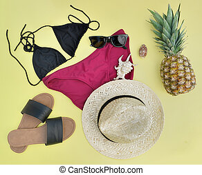 concept of summer vacation with beach accessories and a pineapple on yellow