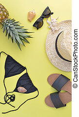 concept of summer vacation with beach accessories and a pineapple on yellow background