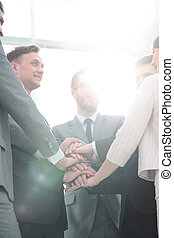 concept of team success: business team standing with folded hand