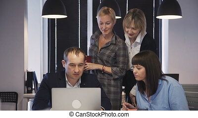 Concept of team work in corporation. Successful and confident people working in modern office with loft interior work place. Mature man and woman using laptop and looking on display